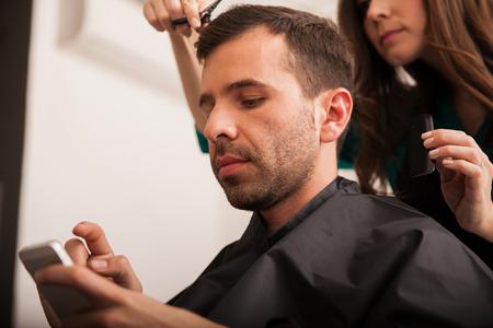 haircut: Young Hispanic man using a smart phone while getting a haircut at a hair salon Stock Photo