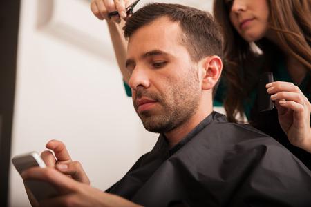 haircut: Young Hispanic man using a smart phone while getting a haircut at a hair salon Stock Photo
