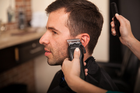 barber shop: Young man getting his sideburns trimmed at a barber shop