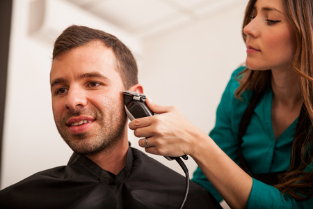 barber shop: Handsome young man getting his sideburns trimmed in a hair salon