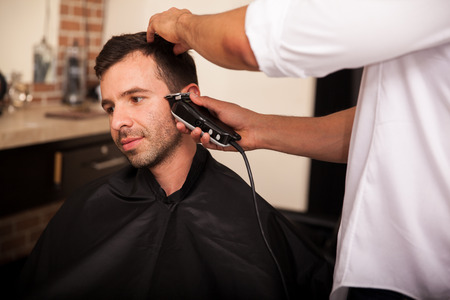 haircut: Young Latin man getting his sideburns trimmed by a barber in a barber shop
