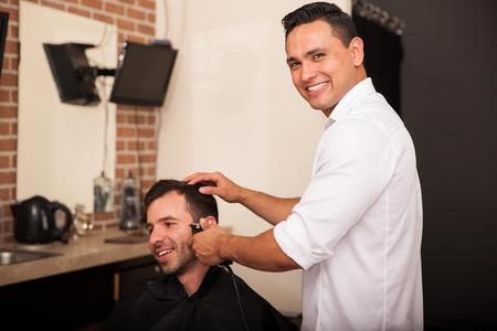 peluquero: Peluquero joven feliz recorte de un cliente Foto de archivo