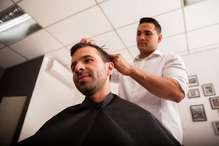 peluquero: Amplio �ngulo de disparo de un hombre joven que consigue un corte de pelo en una peluquer�a Foto de archivo
