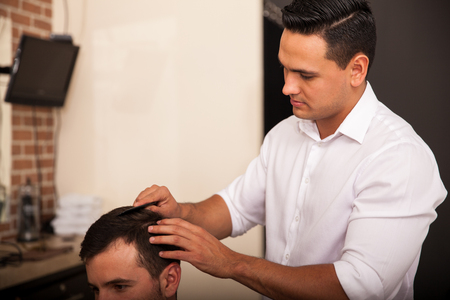 haircut: Handsome young barber giving a haircut to a customer in a barber shop