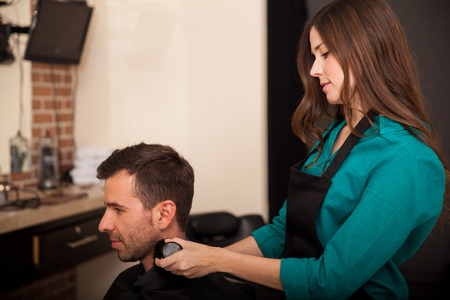 Cute brunette cleaning a customer up with a brush after giving him a haircut in a salon photo