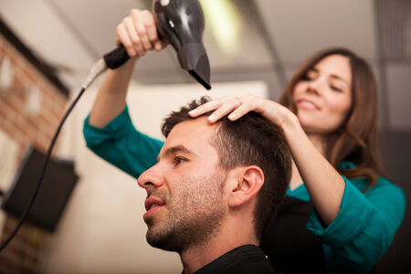 Cute young hairstylist using a blowdryer on some man photo