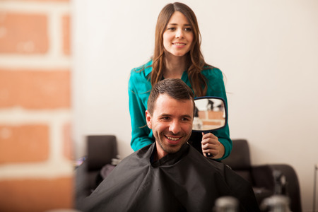 haircut: Happy customer looking at himself in a mirror after getting a haircut in a barber shop