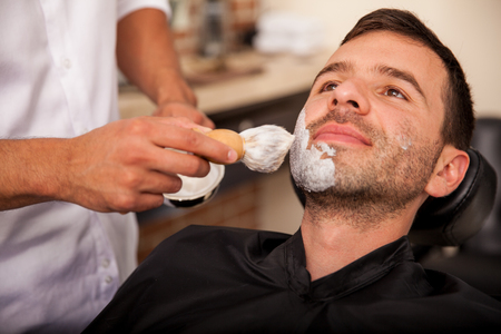 Closeup of a barber putting some shaving cream on a client 写真素材