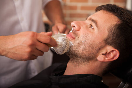Profile view of a barber using a brush to put some shaving cream on a client photo