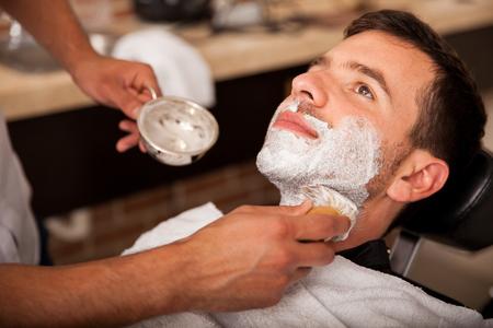 barbero: Relajado hombre joven con crema de afeitar en la cara y listo para conseguir su barba afeitada
