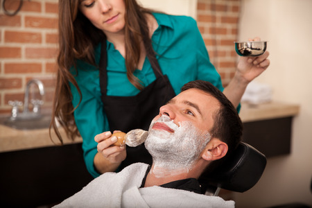 barber chair: Lady barber putting some shaving cream on a client before shaving his beard