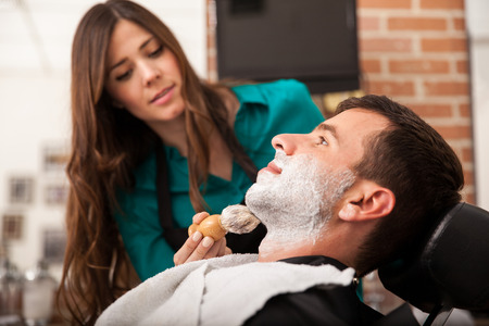 Profile view of a young man about to get a shave from a female barber at a barber shop