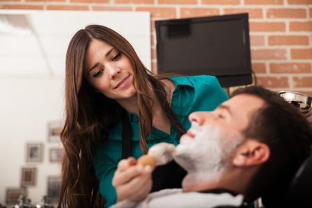 barber shave: Beautiful female barber about to shave a young man and enjoying her work