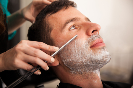 Portrait of a young man getting his beard shaved by a lady barber