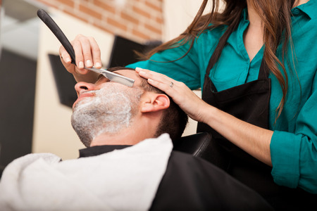 Low angle view of a female barber shaving a man photo