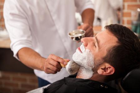 理髪店の彼のひげを剃る前に、クライアントにいくつかのシェービング クリームを入れての理髪師します。