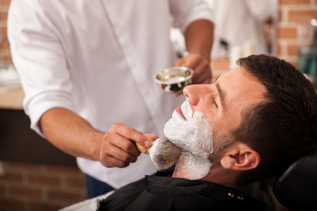 barbeiro: Barber colocar um pouco de creme de barbear em um cliente antes de raspar a barba em uma barbearia