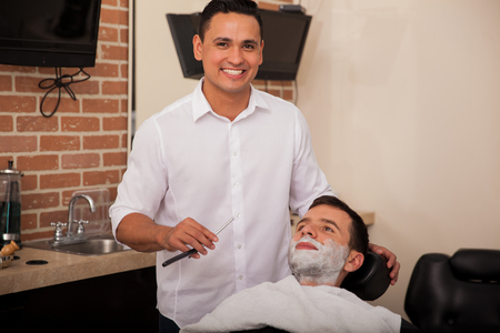 barber shave: Portrait of a handsome young barber holding a razor and about to shave a man