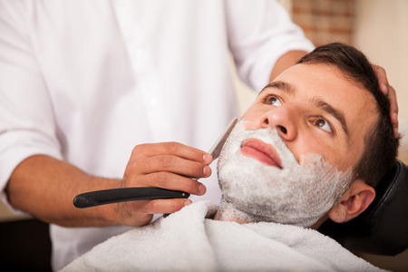 Closeup of a young man getting a close shave at a barber shop photo