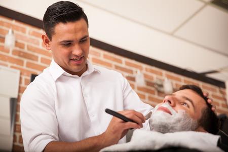 парикмахер: Красивый Латинской парикмахер бритья другого человека