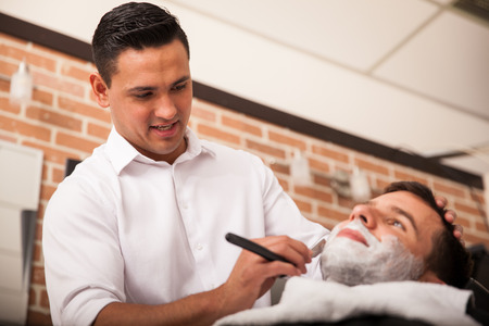 barber chair: Handsome Latin barber shaving another man Stock Photo