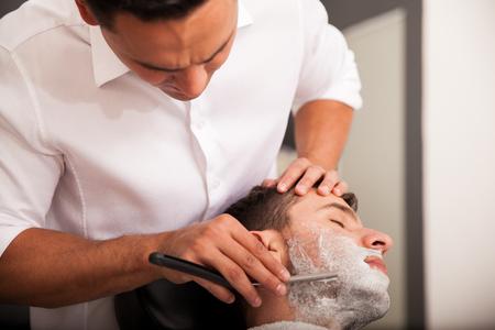 Hispanic man getting his beard shaved in a barber shop