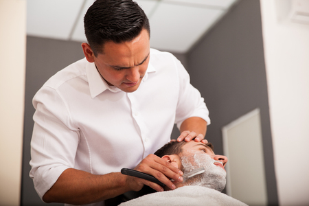 Young barber focusing on shaving a client Stock Photo - 27621631