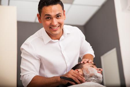 Portret van een jonge kapper scheren een man