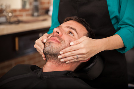 Hispanic man getting a face massage before getting shaved by a lady barber photo