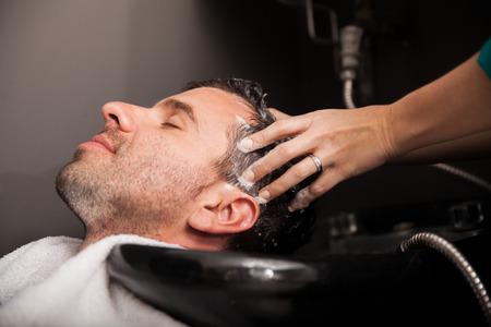 champu: Vista de perfil de un joven obtener su pelo lavado y su cabeza el masaje en un salón de belleza Foto de archivo