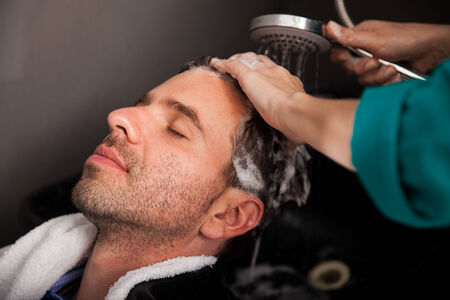 head massage: Young Hispanic man getting pampered with a hair wash and head massage in a hair salon Stock Photo