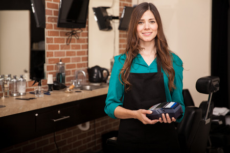 Beautiful brunette holding a credit card terminal in front of a barber shop and smiling 免版税图像