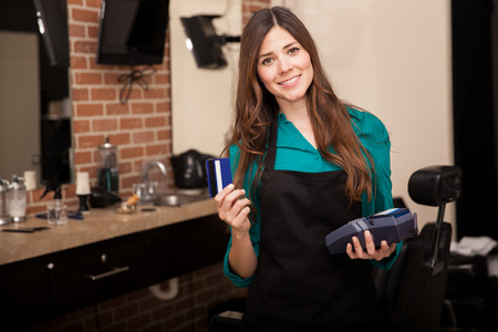Cute young woman holding a credit card and smiling in a barber shop Reklamní fotografie