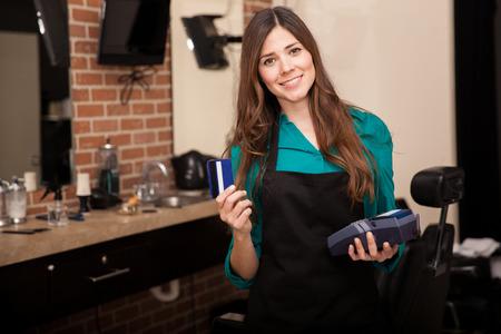 caja registradora: Mujer joven linda celebración de una tarjeta de crédito y sonriendo en una peluquería