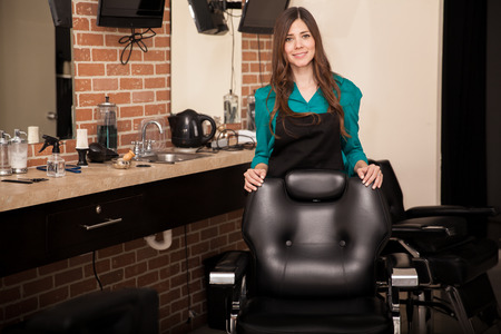 barber chair: Gorgeous young woman standing behind a salon chair and greeting customers to her hair salon