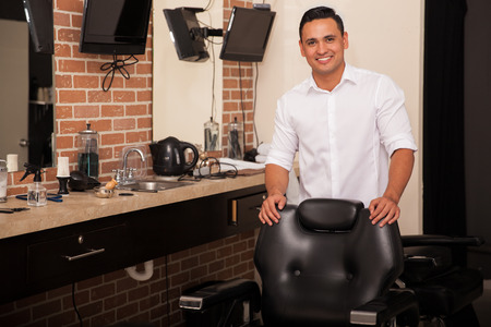 Handsome young barber standing behind a barber chair and greeting clients with a smile