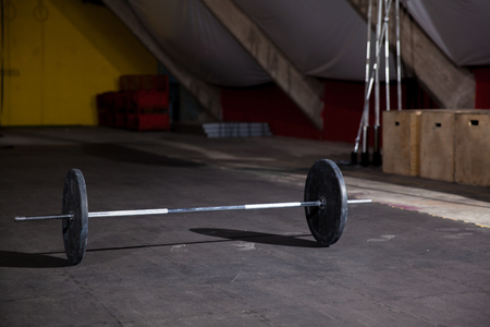 Cross-training gym with a barbell and weights ready for a workout