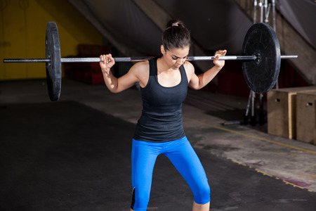 Pretty girl doing some squats with a barbell in a crossfit gym