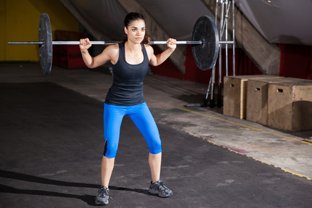 Beautiful Hispanic woman doing some squats with a barbell in a cross-training gym