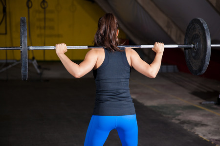 Vista trasera de una mujer joven que hace sentadillas con una barra de pesas en un gimnasio de entrenamiento cruzado Foto de archivo - 28495284