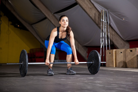 pesas: Hermosa mujer joven levantar algunas pesas como parte de la sesión de entrenamiento del día en un gimnasio crossfit
