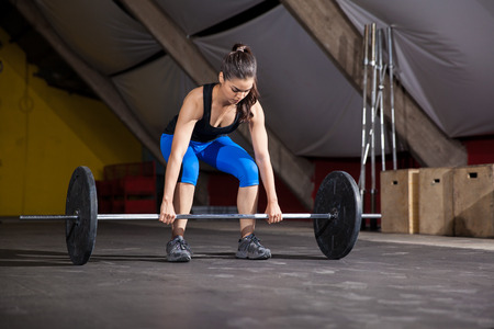 Pretty Latin girl about to lift a barbell during her workout at a cross-training gym photo