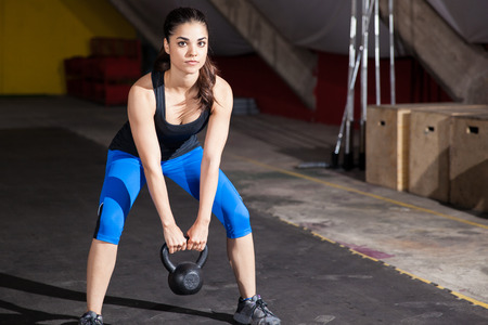 Portrait of a beautiful brunette working out with a kettlebell in a crossfit gym photo