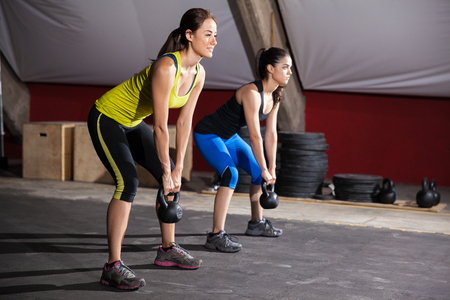 squat: Two young women working out in a cross-training gym using kettlebells
