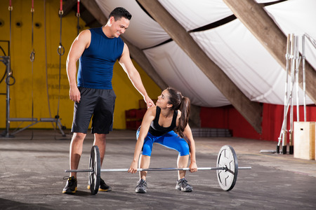 Young Hispanic man giving some advice on her workout to a cute girl in a crossfit gym photo