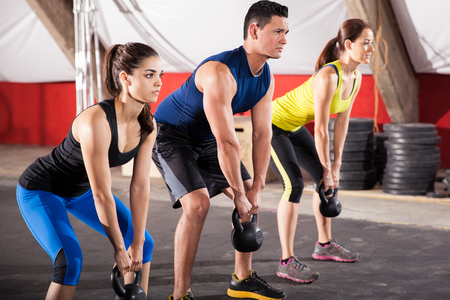 squat: Three people working out with kettlebells in a crossfit gym Stock Photo