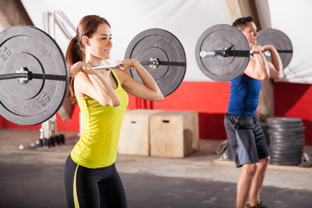 Cute brunette and a guy doing some squats with barbells in a crossfit gym