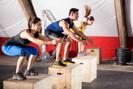 Group of athletic people jumpin over some boxes in a cross-training gym Stock Photo