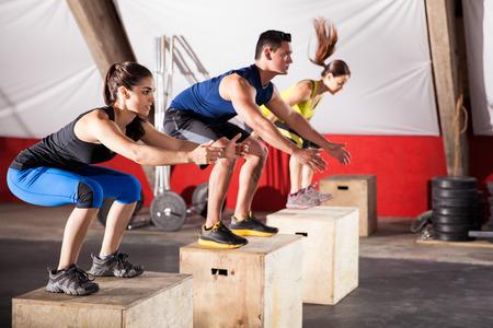 utbildning: Idrotts- gruppfolk jumpin över några lådor i en terränglöpning gym