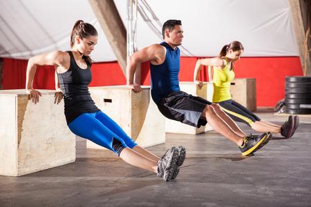 Groep jonge mensen uit te werken hun armen met behulp van dozen in een crossfit sportschool Stockfoto